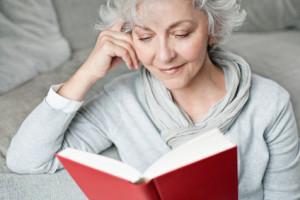 ältere, attraktive Frau genießt ein Buch