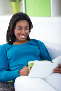 bigstock-Smiling-black-woman-reading-in-43444753